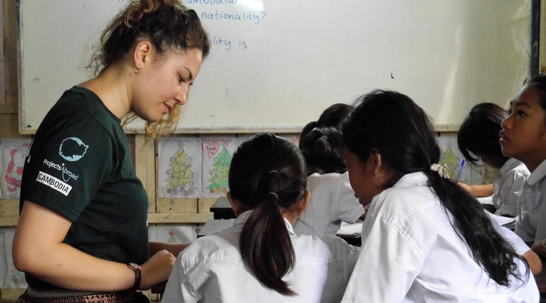 Two students receive class work assistance from a volunteer teaching English in Cambodia